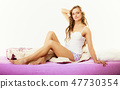 woman long curly hair relaxing on bed at morning 47730354