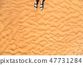 Detail of man legs with sandals on sandy dunes 47731284