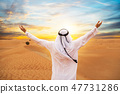 Backview of Arabian man with raised hands 47731286