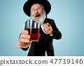 The senior orthodox Jewish man with black hat with Hamantaschen cookies for Jewish festival of Purim 47739146