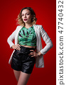 Fashionable female posing in leather shorts on red background 47740432