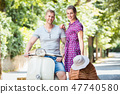 Young couple with scooter and picnic basket 47740580