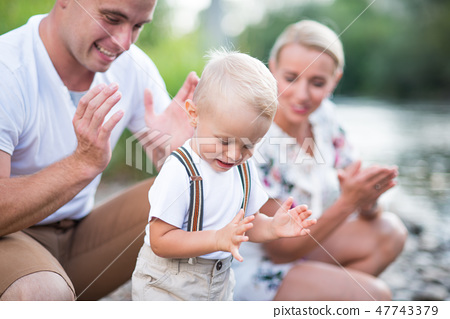 A small toddler boy with his parents outside in sunny summer nature, clapping. 47743379