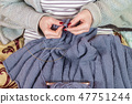woman knits with a smartphone 47751244