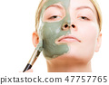 Woman applying with brush clay mud mask her face 47757765