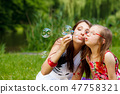 Mother and little girl blowing soap bubbles in park. 47758321