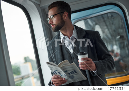 Business trip. Young businessman standing in the train holding newspaper and cup drinking hot coffee 47761534