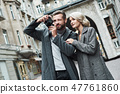 Romantic date outdoors. Young couple walking on the city street taking photos on camera smiling 47761860