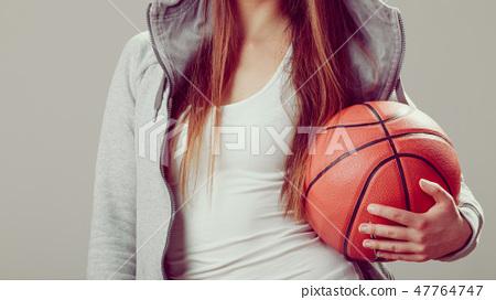 Sporty teen girl in hood holding basketball. 47764747