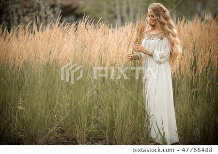 Portrait of happy smiling blonde girl with long blonde hair is wearing white bridal fashion dress on 47768488