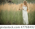 Portrait of happy smiling blonde girl with long blonde hair is wearing white bridal fashion dress in 47768492