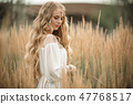Happy smiling blonde girl is wearing white fashion dress with long blonde hair in field of ray 47768517