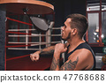 Ready to break his record. Close-up of muscular tattooed boxer in sports clothing hitting punching 47768688