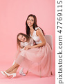 charming mother and smiling daughter on pink background 47769115