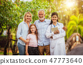 Happy healthy family and doctor talking in park. 47773640