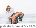 Young couple goes horse riding on tropical beach. 47773976