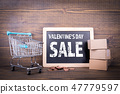 Valentine's Day Sale concept. Paper boxes, chalkboard, shopping carts and cash 47779597
