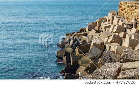 Concrete cubes forming a breakwater against ocean 47787026