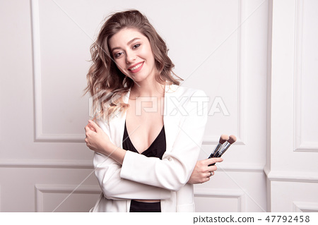 Beautiful young girl with brown hair in her hands holding a professional makeup brush 47792458