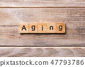 Aging word written on wood block 47793786