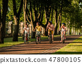 Young sporty active people biking in park. 47800105