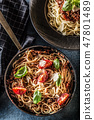 Top of view italian pasta spaghetti bolognese in plate and pan with tomatoes and basil 47801489