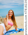Woman on beach talking by mobile phone. 47818220