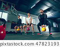 The strong young fitness men in sportswear doing exercises at gym 47823193