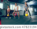 The strong young fitness men and women in sportswear doing exercises at gym 47823194