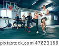 Shot of young men and a woman standing in plank position at the gym 47823199