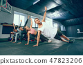 Shot of young men and a woman standing in plank position at the gym 47823206