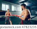 Two muscular athletes training, working out with rope 47823235