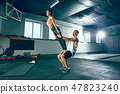 Shot of young man and a woman standing in plank position at the gym 47823240