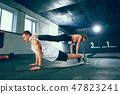 Shot of young man and a woman standing in plank position at the gym 47823241