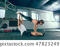 Shot of young man and a woman standing in plank position at the gym 47823249