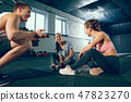 Portrait of young people resting and looking at camera after training session in gym. 47823270