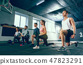 Shot of young men and a woman standing in plank position at the gym 47823291