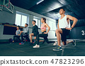 Shot of young men and a woman standing in plank position at the gym 47823296