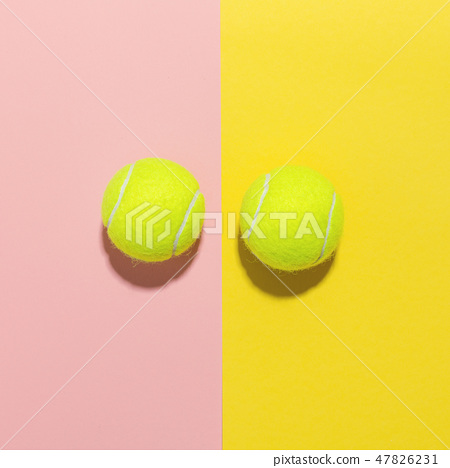 Tennis balls flat lay on pink and yellow 47826231