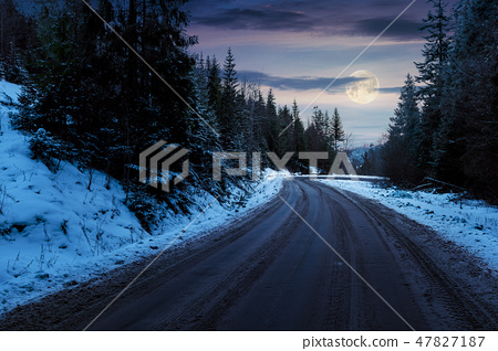 road through forest in mountains at night 47827187