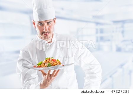 Chef in restaurant kitchen holding plate with meal 47827282