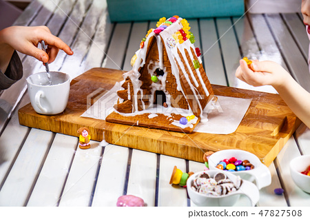 Familiy building a sweet ginger bread house 47827508