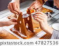 Familiy building a sweet ginger bread house 47827536
