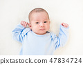 Newborn lovely cute baby lying on white bed sheet 47834724