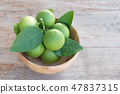 Fresh branch of limes in wood bowl on old wood 47837315