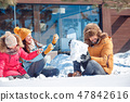 Winter vacation. Family time together outdoors sitting playing with snow laughing cheerful 47842616
