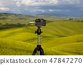 Dslr camera photographing Tuscany hills 47847270