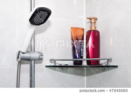 욕실에 있는 물이 나오지 않는 샤워기와 샴푸 47848060