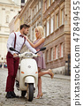 Love couple on the street with retro scooter 47849455