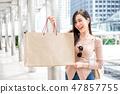 Beautiful young Asian woman holding a shopping bag 47857755